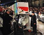 原波兰团结工会主席和民主波兰第一任民选总统瓦文萨,推动了竖在国会大厦附近的第一块象征柏林墙的多米诺骨牌。(法新社)