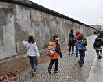 1989年11月9日,分隔东西柏林和东西德的柏林墙倒塌,促进了东西德的统一,随后全世界的共产阵营也陆续垮台。图为2009年柏林墙倒塌20周年时,人们走过部分保留下来的柏林墙。(李家祥FEFERBERG/法新社)