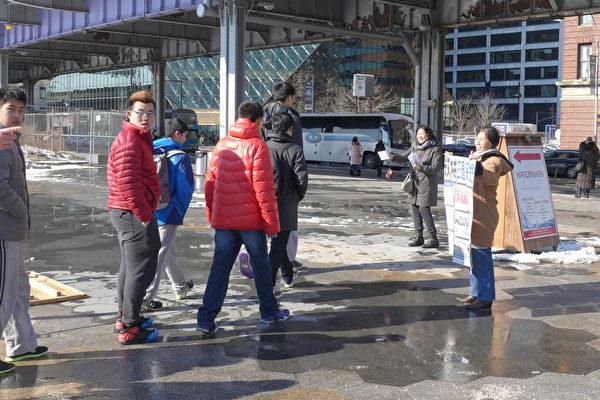 近幾年來,來17碼頭的遊覽的大陸中學生團特別多,由老師帶隊出來。退黨義工通過各種方式讓大陸游客了解真相,包括手舉真相展板、播放真相廣播、發小冊子、掛橫幅等等,圖為義工王女士和唐女士在向遊客展示真相資料。(蔡溶/大紀元)
