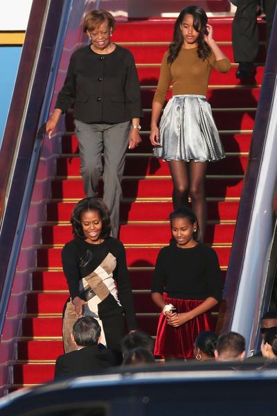 北京时间20日,米歇尔和二个女儿以及母亲罗宾逊在北京机场上亮相。米歇尔未有发表公开讲话。( Feng Li/Getty Images)