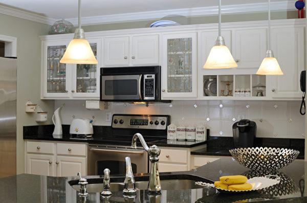 白色的橱柜表现出厨房的整洁,同时白色也可以起到放大空间的作用;黑色的台面让厨房显露出低调的华丽;暖黄的灯光让人有种温暖的家的感觉。(图/Fotolia)