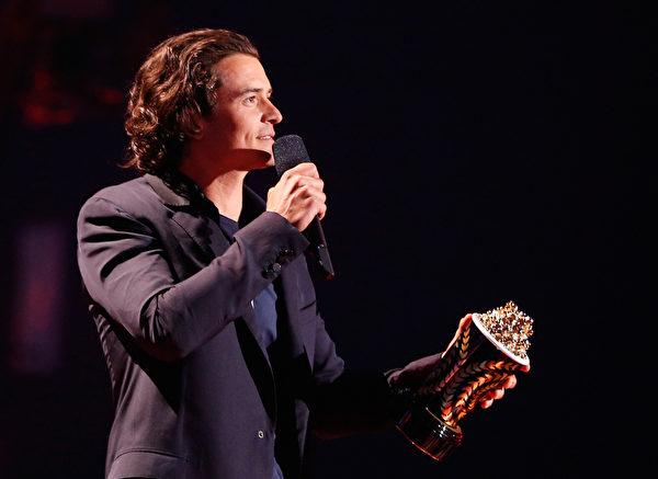 2014年4月13日,MTV电影奖颁奖典礼,凭《霍比特人:史矛革之战》获最佳打戏奖的奥兰多•布鲁姆上台领奖。(Christopher Polk/Getty Images for MTV)