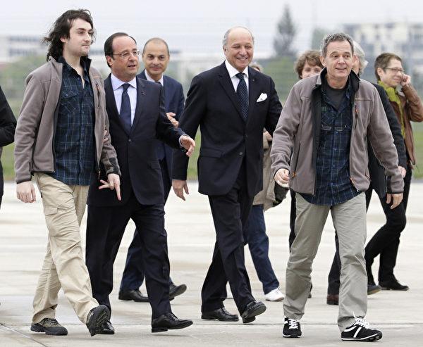 去年在敘利亞遭綁架的4名法國記者,已在2014年4月18日獲釋,並於20日返抵巴黎。本圖為法國總統奧朗德(左二)及外交部長法比尤斯(右二)前往空軍機場接機。(AFP PHOTO / KENZO TRIBOUILLARD)