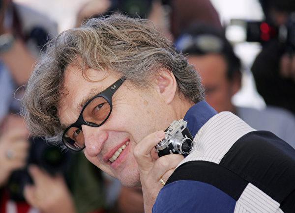 维姆·文德斯2005年在戛纳影展记者会上举起相机。(GERARD JULIEN/AFP/Getty Images)