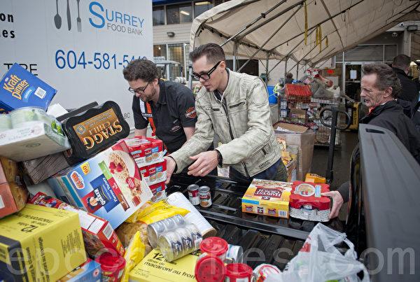 汽車經銷集團 Barnes Wheaton籌到滿滿兩輛GMC皮卡的捐贈物品,包括食物、嬰兒用品和現金。(攝影:大宇/大紀元)