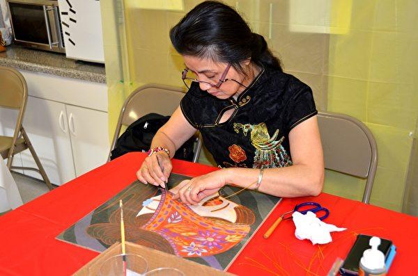 来自中国深圳红梅琴工艺坊的金梅女士在演示制作景泰蓝工艺画。(良克霖/大纪元)