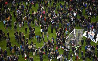 事發後,足球迷們聚集於球場的中心以保安全。 (FRANCK FIFE/AFP/Getty Images)