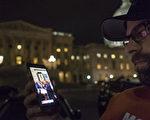 2016年6月23日,美國民主黨眾議員要求眾議院就槍枝安全法表決,發起維持長達12個小時的靜坐,圖為一名支持者在國會大廈外通過手機觀看在眾議院內共和黨人靜坐的現場直播。(Pete Marovich/Getty Images)
