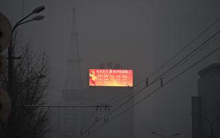 共產黨在電子廣告牌上打出的宣傳標語在北京陰霾的襯托下格外諷刺。(GREG BAKER/AFP/Getty Images)