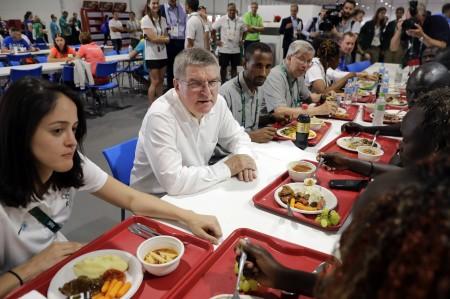 图为8月1日,国际奥委会主席托马斯·巴赫(中左)和难民奥运代表队的成员在里约奥运村的餐厅进餐时聊天。  (PATRICK SEMANSKY/AFP/Getty Images)