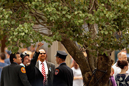 NEW YORK, NY - SEPTEMBER 11: New York Fire Department fire fighters look at the 9/11 survivor tree at the 9/11 Memorial Plaza during the tenth anniversary ceremonies of the September 11, 2001 terrorist attacks at the World Trade Center site, September 11, 2011 in New York City. New York City and the nation are commemorating the tenth anniversary of the terrorist attacks which resulted in the deaths of nearly 3,000 people after two hijacked planes crashed into the World Trade Center, one into the Pentagon in Arlington, Virginia and one crash landed in Shanksville, Pennsylvania. (Photo by Chip Somodevilla/Getty Images)