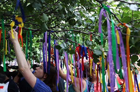 NEW YORK, NY - JUNE 16: People tie ribbons on the Survivor Tree at the National September 11 Memorial & Museum in honor of the victims of the Orlando nightclub attack on June 16, 2016 in New York City. Hundreds of people tied colored ribbons on the Survivor Tree at the National September 11 Memorial & Museum to honor the victims of the terror attack at the Pulse nightclub in Orlando over the weekend that left 49 dead. (Photo by Justin Sullivan/Getty Images)