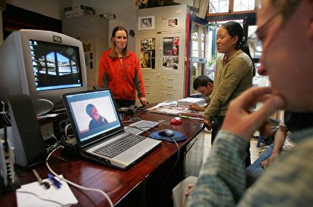 """TO GO WITH """"CHINA-TIBET-GERMANY-PEOPLE-DISABLED""""Sabriye Tenberken (L) of and her partner Paul Rosenberg (R), who is not blind, listen and watch a promotional video of student Kumi (3rd R), 11, singing """"Happy Together"""" as student Yudon (2nd R) listens, 07 August 2005, at the Training Center for the Blind the school in Lhasa, Tibet. Yudon is one of 76 students at the Training Center for the Blind the school, a unique experiment started and run by 34-year-old German Sabriye Tenberken, who herself has been blind since the age of 12. AFP PHOTO/Frederic J. BROWN / AFP PHOTO / FREDERIC J. BROWN"""