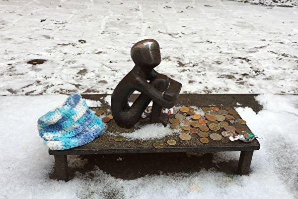 """看月亮的男孩(Pojke som tittar på månen)又名""""铁男孩""""(Järnpojke)。位于斯德哥尔摩老城。由雕塑家李斯。埃里克松(Liss Eriksson )于1967年创作。雕塑高15厘米。他是最受游客喜爱的男孩形象。经常有游客留下硬币和糖果,也有游客会在天冷的时候带来特意编织的小帽子、小围巾给他戴上。(雨莲/大纪元)"""