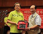 台北市龙门扶轮社社长苏瑞泉(左)捐赠(AED)20组予宜兰县政府。(谢月琴/大纪元)