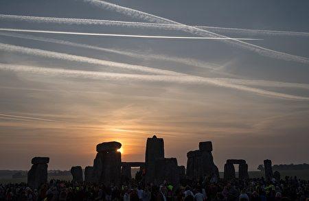 6月21日夏至日的早晨,大批人聚集在巨石阵等待日出。这个活动的历史可以追溯到几千年以前。人们到现在还不清楚巨石阵存在的目的,但是人们知道在夏至日这天,光线会从巨石阵前方像拱门一样的鞋跟石中间直射到巨石阵中间的祭坛石。人们一边观看这个奇景,一边感叹古人的智慧。(CHRIS J RATCLIFFE/AFP/Getty Images)