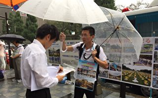 日本部分法輪功學員8月15日,在東京九段下車站擺真相看板,向民眾講真相,並徵集聯署舉報江澤民的簽名,儘管當天遇到大雨,依然有上千名的日本民眾和外國遊客在聯署舉報書上簽了名。(英傑/大紀元)