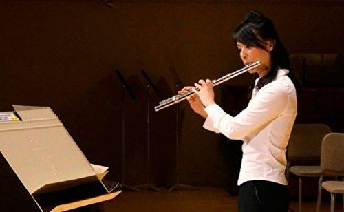 李佳蓉在練習長笛。(神韻藝術團官網提供)
