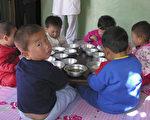 今年第二季中国向朝鲜出口粮食同比增长大幅上升,专家说,很可能是为了满足朝鲜精英层的口腹之欲,朝鲜人民仍在挨饿。图为接受国际粮食援助的朝鲜孩童。(Gerald Bourke/WFP via Getty Images)