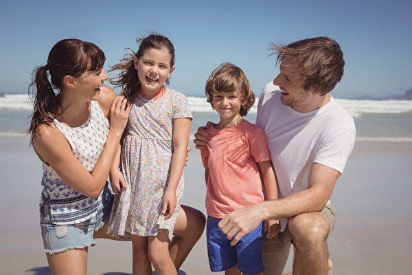 與父母在海灘愉快的兄弟姐妹