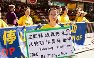 纽约法轮功学员张玉华21日在联合国门前举牌呼吁营救他两天前刚被抓走的丈夫、南京法轮功学员马振宇。(戴兵/大纪元)
