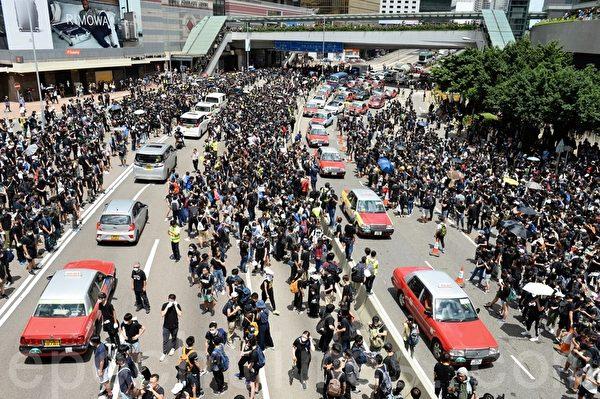 由於港府在6月20日下午 5 時「死線」前未回應示威者的訴求,學界及民間6月21日昇級抗議行動,包圍灣仔警察總部。上午 11 時左右,大批示威者衝出夏愨道路面,全面佔據夏愨道東西行車線。(宋碧龍/大紀元)