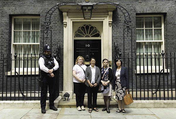 7月20日下午,英國法輪大法協會代表和幾名曾親身遭受中共迫害的先旅居英國的法輪功學員在唐寧街十號首相府門前合照。(冠奇/大紀元)