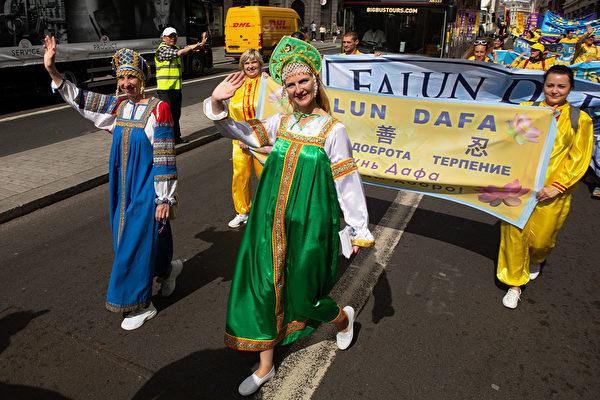 8月30日,俄羅斯法輪功學員Julia Zaitsebov 身著俄羅斯傳統服飾走在當天遊行隊伍當中,向當地民眾展現法輪大法的美好。(傅潔/大紀元)