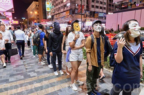 2019年10月18日,香港市民在彌敦道組人鏈。圖為抗爭者戴各種公仔面具。(宋碧龍/大紀元)