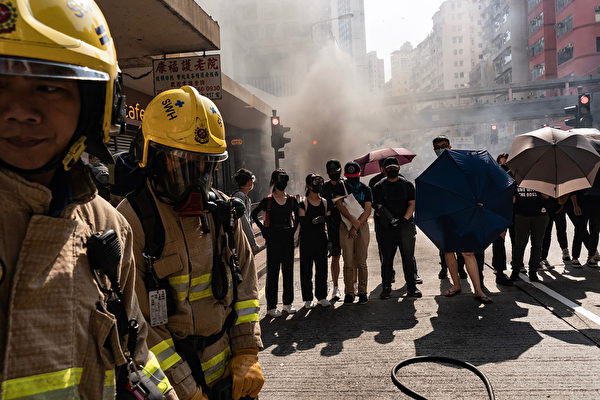 """HONG KONG, CHINA - November 11:Protesters hold umbrellas as they block firefighters from accessing a burning roadblock on November 11, 2019 in Hong Kong, China. Anti-government protesters organized a general strike on Monday as demonstrations in Hong Kong stretched into its sixth month with demands for an independent inquiry into police brutality, the retraction of the word """"riot"""" to describe the rallies, and genuine universal suffrage. (Photo by"""