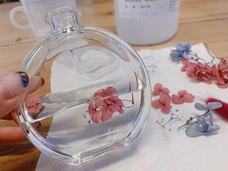 將花材與保存油交錯堆疊放入,形塑想要呈現的樣子。