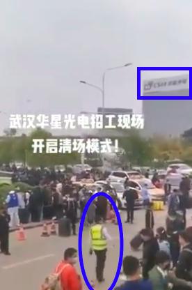 視頻背景是武漢華星光電的大樓。圖中橢圓形藍框裡的人,就是疑似工作人員。(視頻截圖)