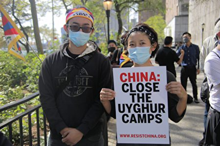"""民众在纽约联合国总部附近手举标语""""要中共关闭拘留维吾尔人的集中营""""。"""