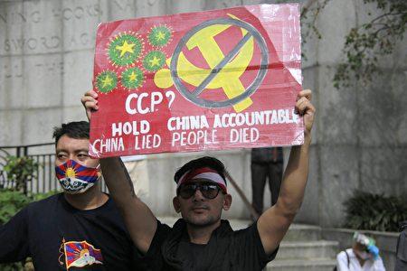"""民众在纽约联合国总部附近手举标语""""要中共对疫情负起责任""""。"""