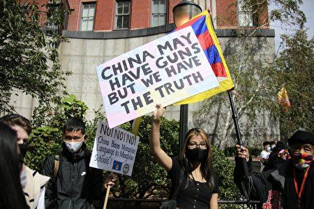 """民众在纽约联合国总部附近手举标语""""中共可能有枪,但我们有真相""""。"""