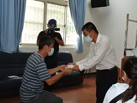 鑫永銓股份有限公司董事長林季進(右)親自發放急難救助金給疫情受害邊緣戶每人萬元。